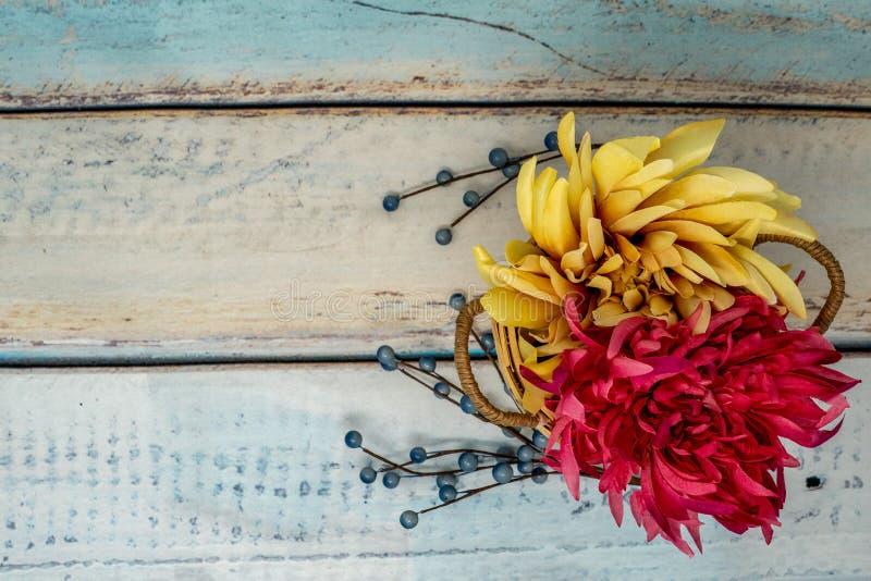 Os mums amarelos e vermelhos florescem em uma cesta com bagas azuis azul imagens de stock