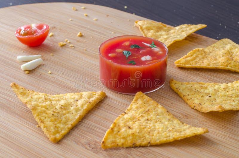 Os nachos do petisco com alho e salsa do tamato mergulham imagem de stock