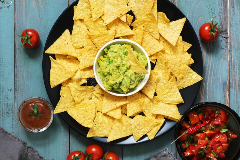 Os nachos mexicanos lascam-se com molho e guacamole da salsa no fundo rústico foto de stock royalty free