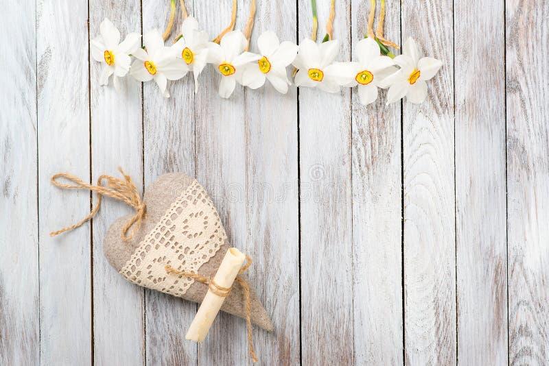Os narciso florescem, coração decorativo em um fundo de madeira claro Foco seletivo Espaço para o texto imagem de stock