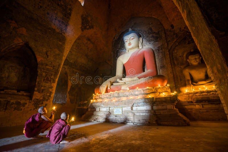 Os neófitos asiáticos do sudeste iluminam velas dentro de um templo budista foto de stock