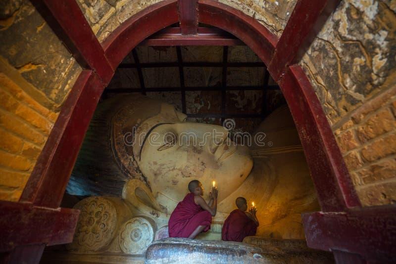 Os neófitos asiáticos do sudeste iluminam velas dentro de um templo budista imagem de stock