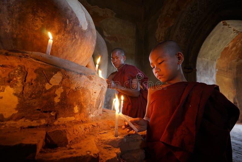 Os neófitos asiáticos do sudeste iluminam velas dentro de um templo budista fotografia de stock royalty free