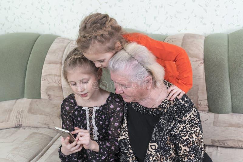 Os netos ensinam a bisavó usar o smartphone imagens de stock