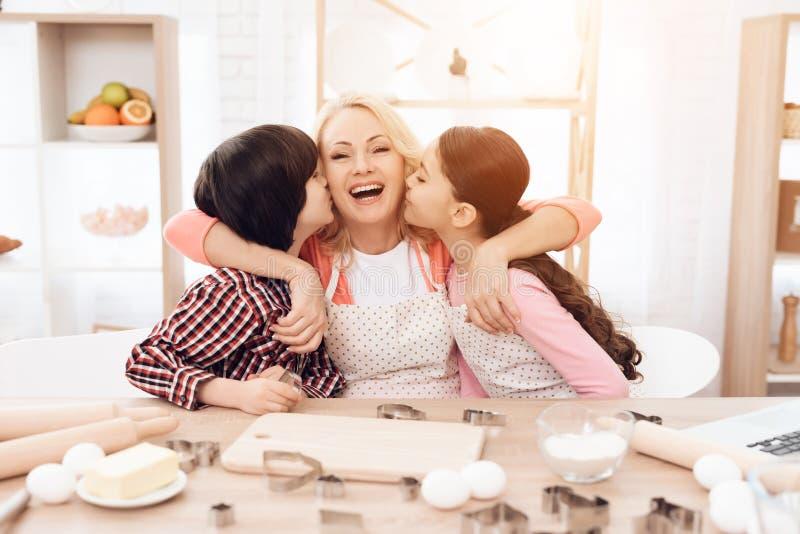 Os netos pequenos beijam a avó bonita que senta-se na cozinha Cookies do cozimento foto de stock royalty free