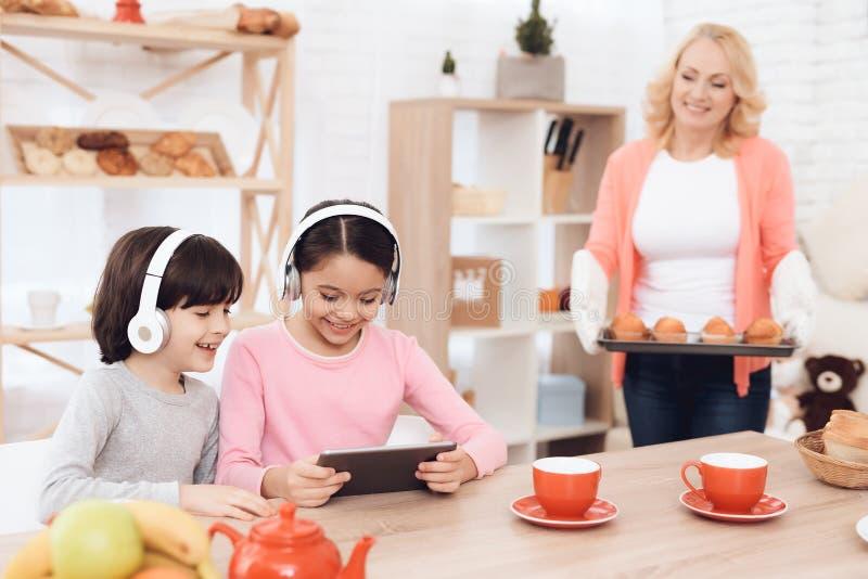 Os netos pequenos nos fones de ouvido olham a tabuleta na cozinha de minha avó, que cozinhou queques imagem de stock