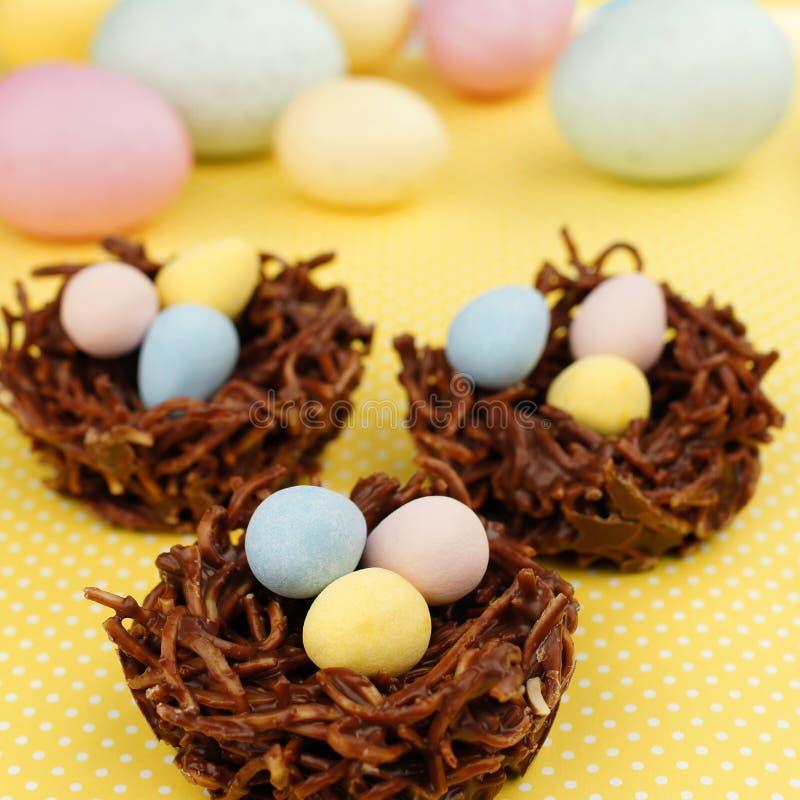Os ninhos do chocolate da primavera encheram-se com os ovos da páscoa no amarelo fotografia de stock royalty free