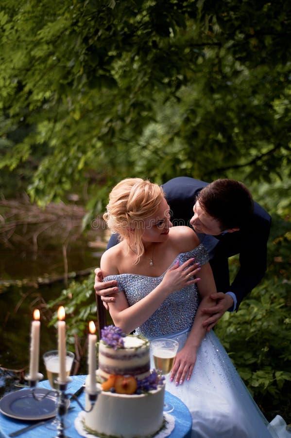 Os noivos sentam-se em uma tabela pela água Decoração em tons azuis, na tabela um bolo de dois níveis, em vidros e em velas imagens de stock