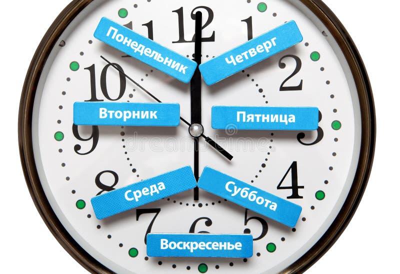 Os nomes dos dias da semana no russo encontram-se no fundo da face do relógio foto de stock