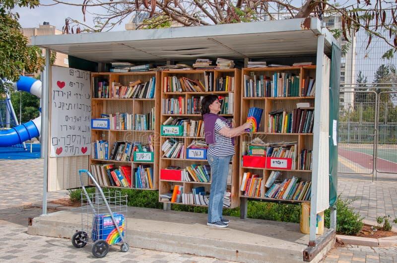 Os novos livros estão sendo colocados na biblioteca exterior em Ness Ziona imagens de stock royalty free