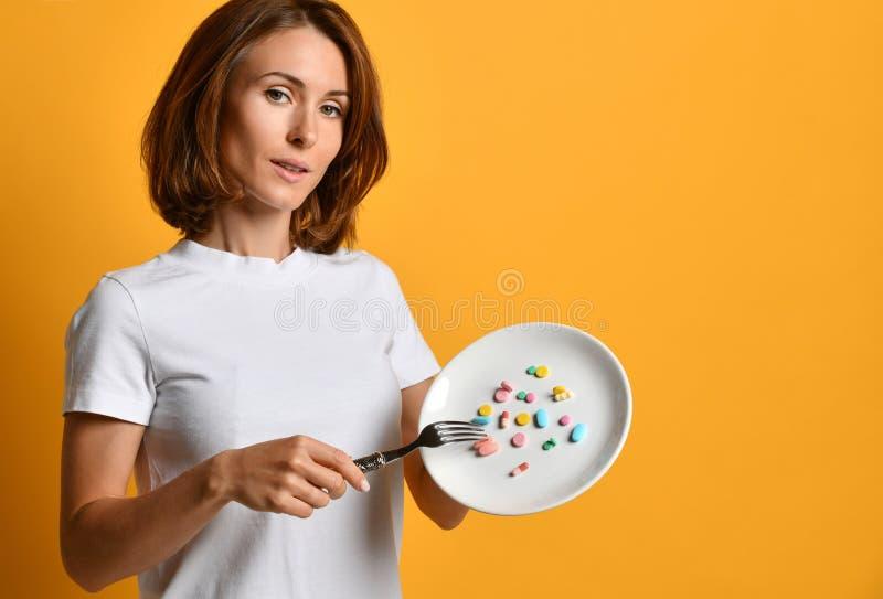 Os nutritionis da mulher tomam com as drogas diferentes de uma perda de peso dos comprimidos da cor dos suplementos dietéticos da fotos de stock
