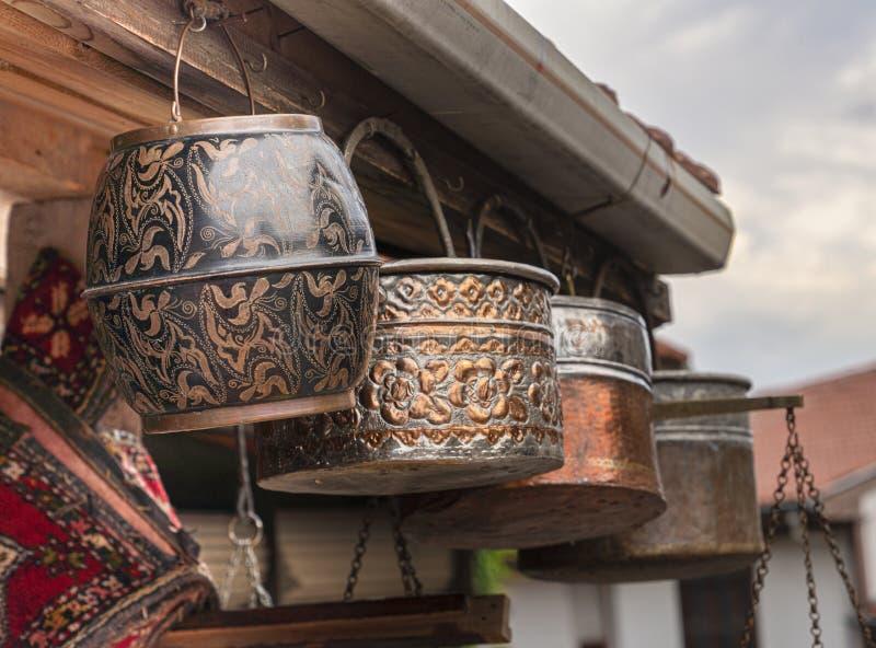 Os objetos antigos feitos a mão, forjaram as cubetas de cobre que penduram na frente da loja/bazar na rua imagens de stock royalty free