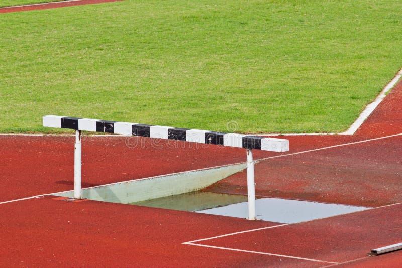 Os obstáculos na pista de atletismo vermelha prepararam-se para a competição. fotos de stock