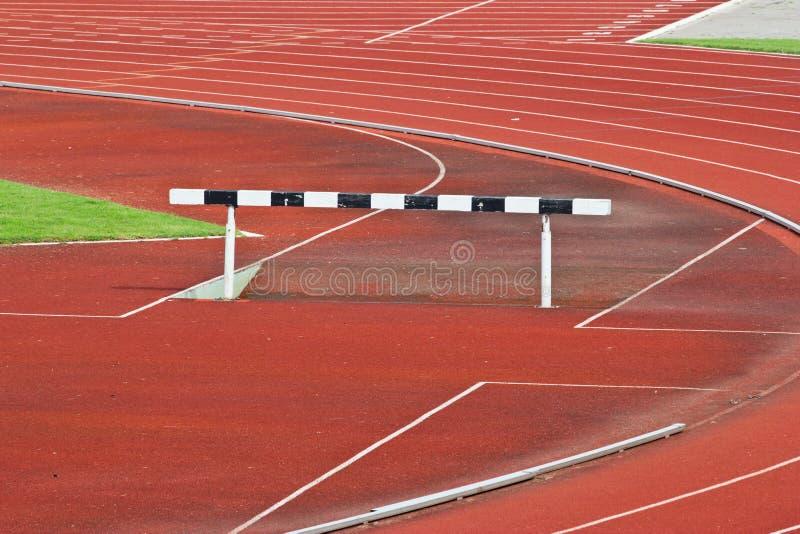 Os obstáculos na pista de atletismo vermelha prepararam-se para a competição. imagem de stock