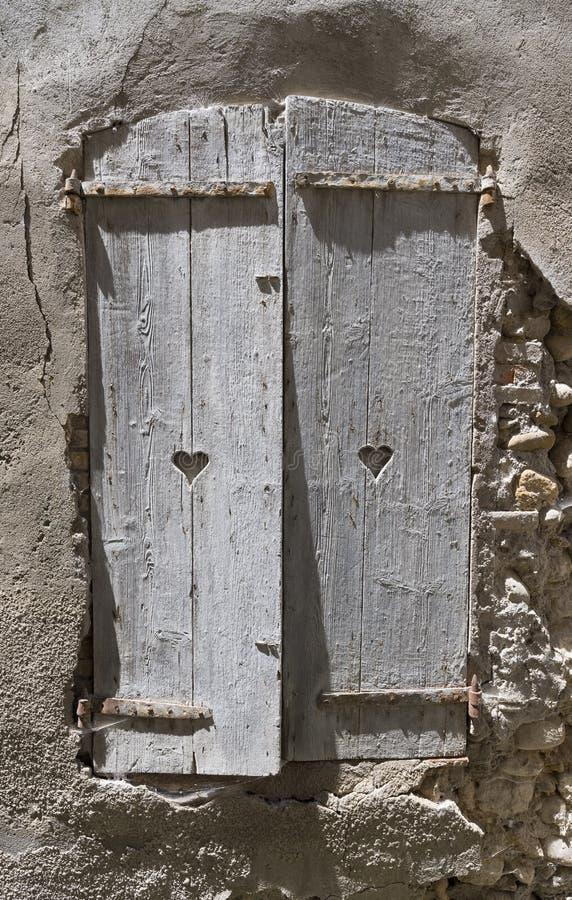 Os obturadores cinzentos velhos com coração deram forma a furos na parede antiga da construção medieval na cidade do riez no fran fotos de stock