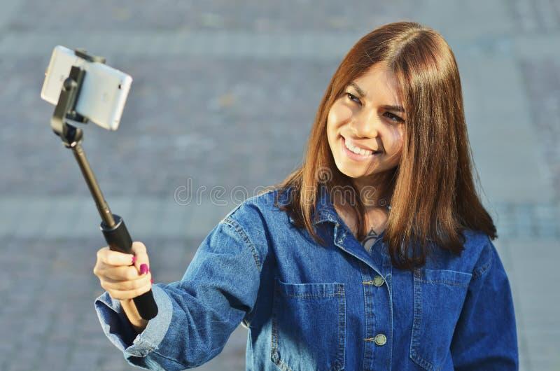 Os olhares asi?ticos da menina moreno em um terno da sarja de Nimes tomam um selfie imagens de stock