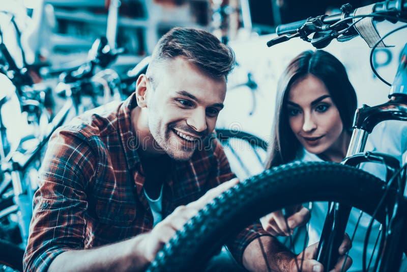 Os olhares da menina e do indivíduo na bicicleta rodam dentro a loja do esporte fotografia de stock