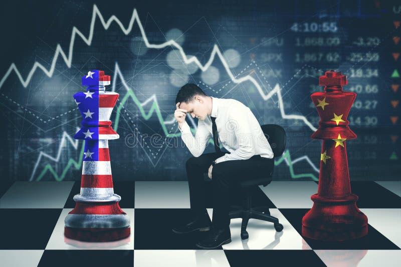 Os olhares novos do homem de negócios forçaram com guerra comercial foto de stock