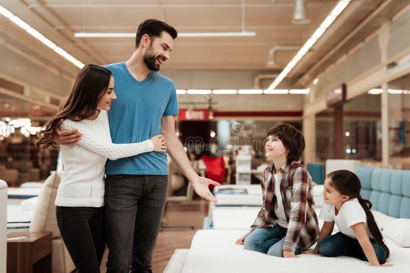 Os olhares novos dos pares como crianças estão sentando-se no colchão na loja de móveis Família feliz que escolhe colchões na loj imagens de stock royalty free
