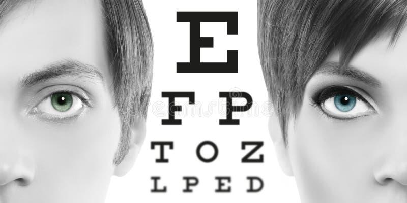 Os olhos azuis fecham-se acima na carta de teste, na visão e no exame de olho visuais foto de stock