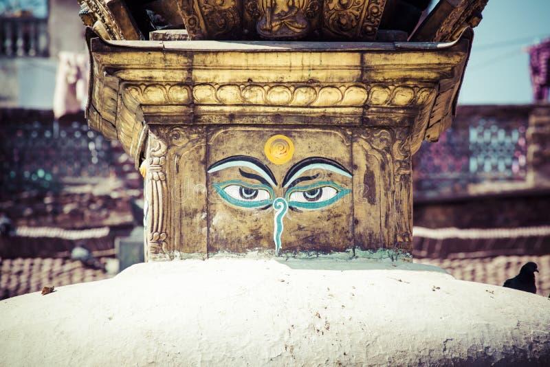 Os olhos da Buda fecham-se acima com as bandeiras da oração no stupa de Bodhnath em Kath fotografia de stock