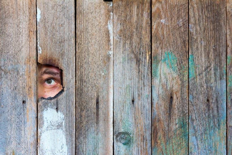 Os olhos de um homem que espia através de um furo imagem de stock