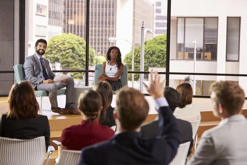 Os oradores masculinos e fêmeas do seminário tomam a pergunta da audiência imagens de stock royalty free