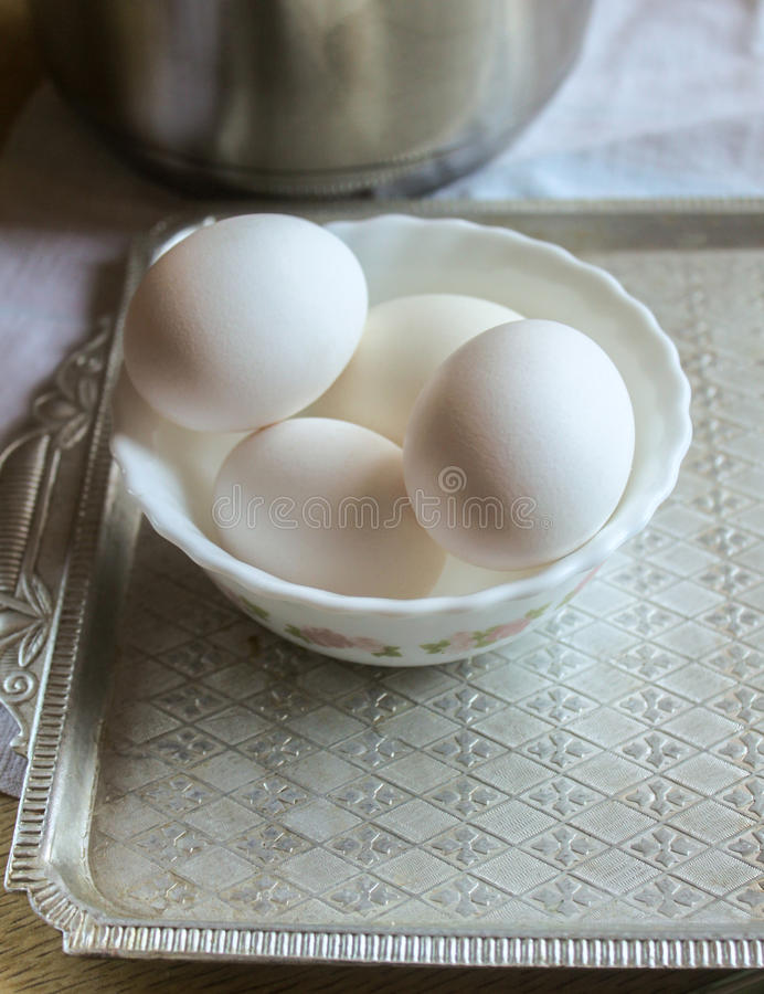 Os ovos brancos encontram-se em uma bacia com um número de bandeja ereta fotografia de stock