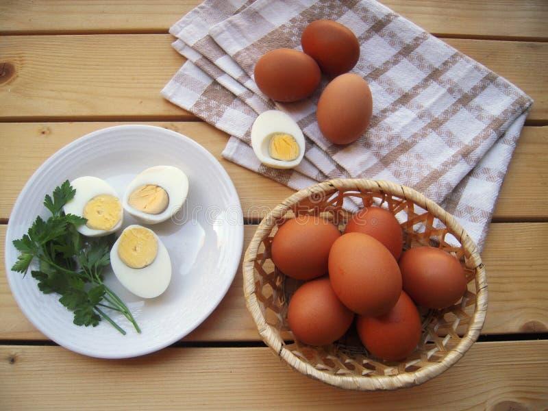 Os ovos cortaram em uma placa, na cesta e na toalha de cozinha em uma tabela de madeira, styl rústico imagem de stock