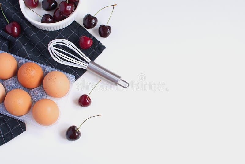 Os ovos crus batem cerejas maduras do ramekin branco e do guardanapo quadriculado imagem de stock