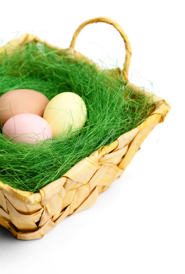 Os ovos da páscoa coloridos estão em cesta trançada imagem de stock