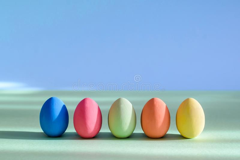 Os ovos da páscoa coloridos estão estando em seguido fotografia de stock
