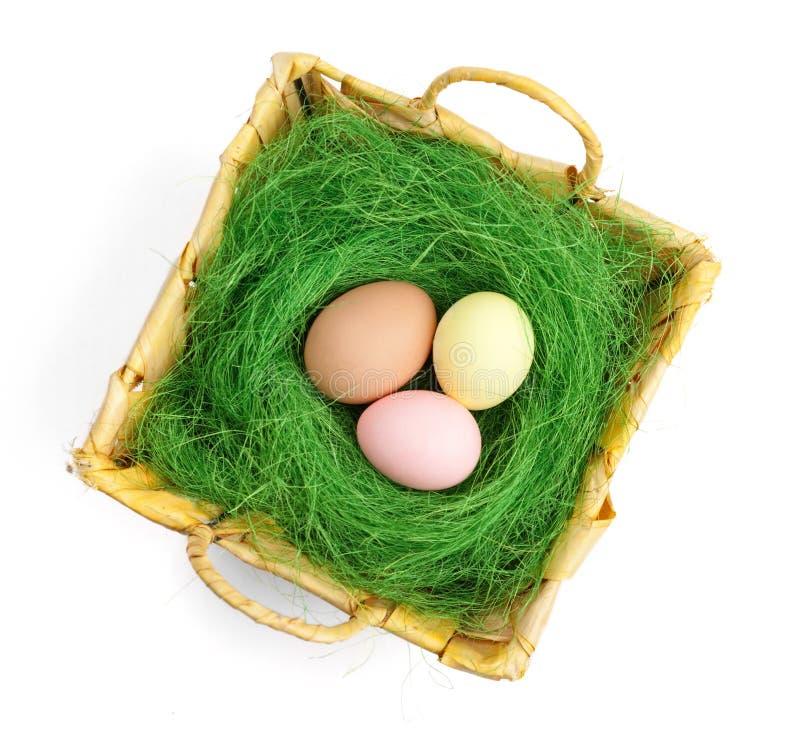 Os ovos da páscoa coloridos estão na cesta wattled fotos de stock royalty free