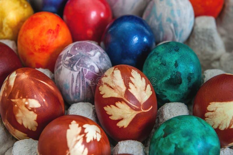 Os ovos da páscoa coloridos pintados estão nas pilhas na caixa Fundo fotos de stock