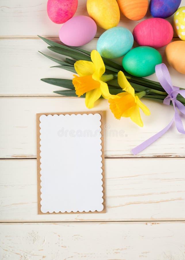 Os ovos da páscoa e o narciso amarelo coloridos florescem a vida imóvel no fundo rústico da placa branca com o cartão vazio do me imagens de stock