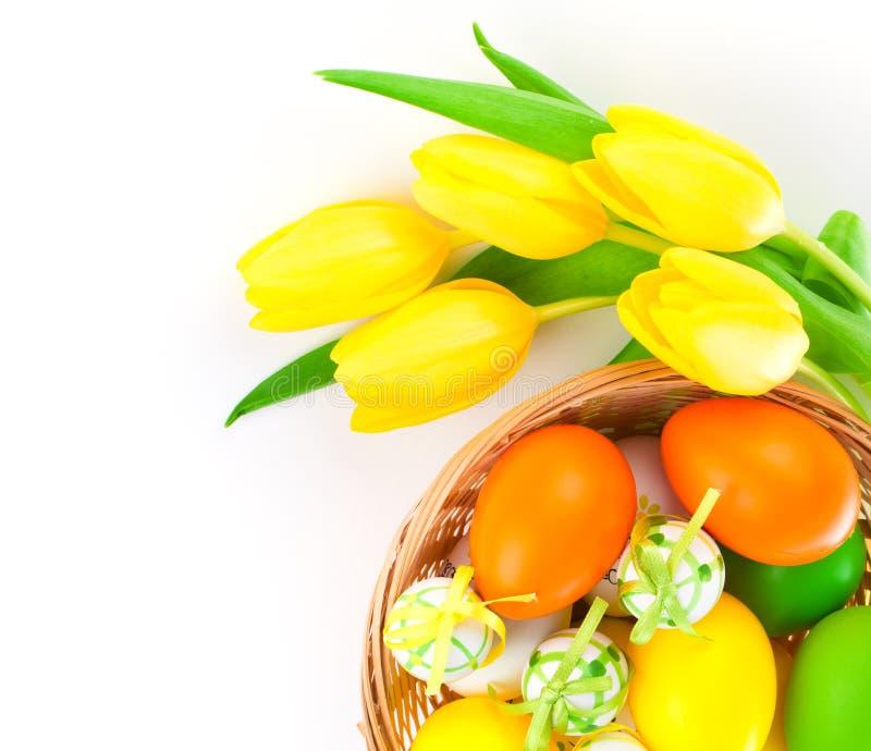 Os ovos da páscoa em uma cesta com tulipas amarelas florescem imagem de stock