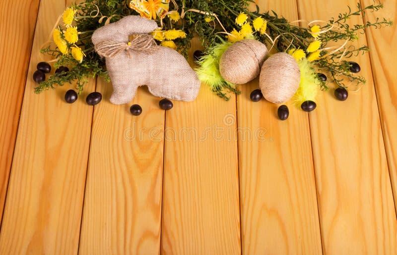 Os ovos da páscoa entrelaçaram-se com corda, coelho, drageias, flores, grama fotografia de stock