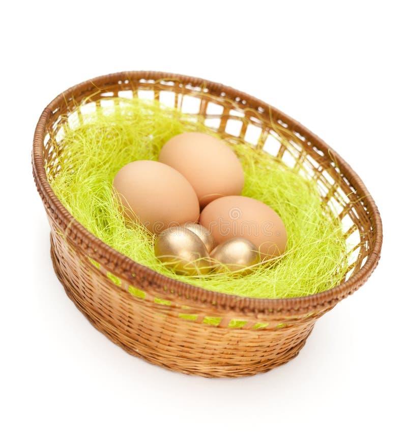 Os ovos da páscoa estão na cesta wattled foto de stock