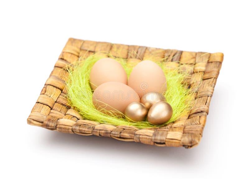 Os ovos da páscoa estão na placa wattled quadrado foto de stock royalty free