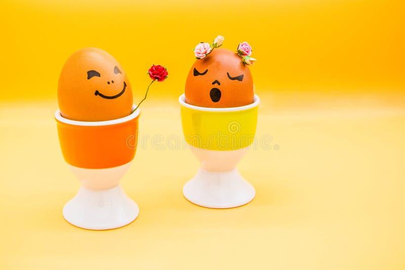 Os ovos da páscoa felizes com desenhos animados tirados pintados enfrentam em claro - fundo amarelo O menino dá a flor da rosa da imagem de stock royalty free