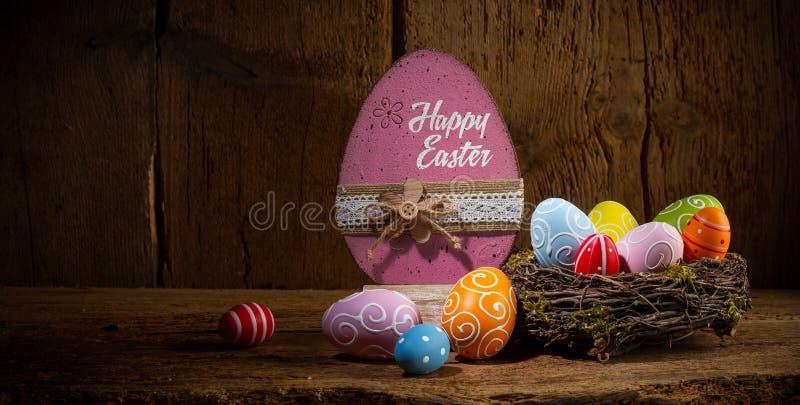 Os ovos da páscoa felizes pintados coloridos nos pássaros aninham a cesta no espaço velho de madeira rústico da cópia do fundo do fotos de stock