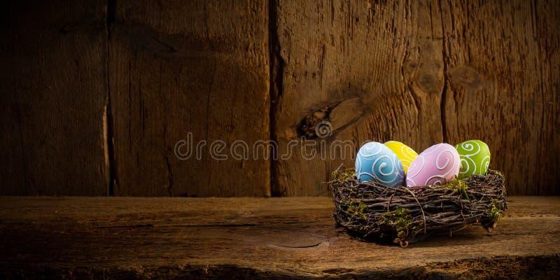 Os ovos da páscoa felizes pintados coloridos nos pássaros aninham a cesta no espaço velho de madeira rústico da cópia do fundo do fotografia de stock