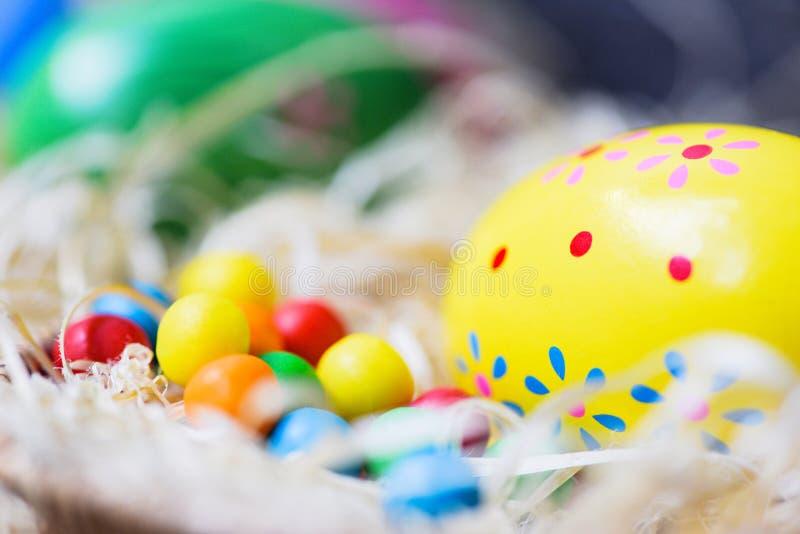 Os ovos da páscoa no fundo da cesta do ninho pintaram o ovo colorido decorado com os doces coloridos dos doces fotografia de stock royalty free