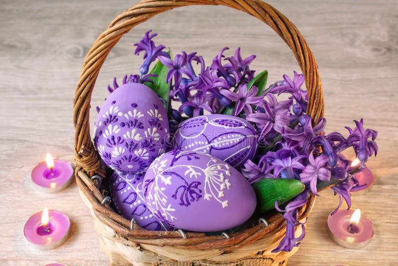 Os ovos da páscoa pintaram em uma cesta com as flores em tons lilás, e em velas ao redor em um fundo de madeira foto de stock