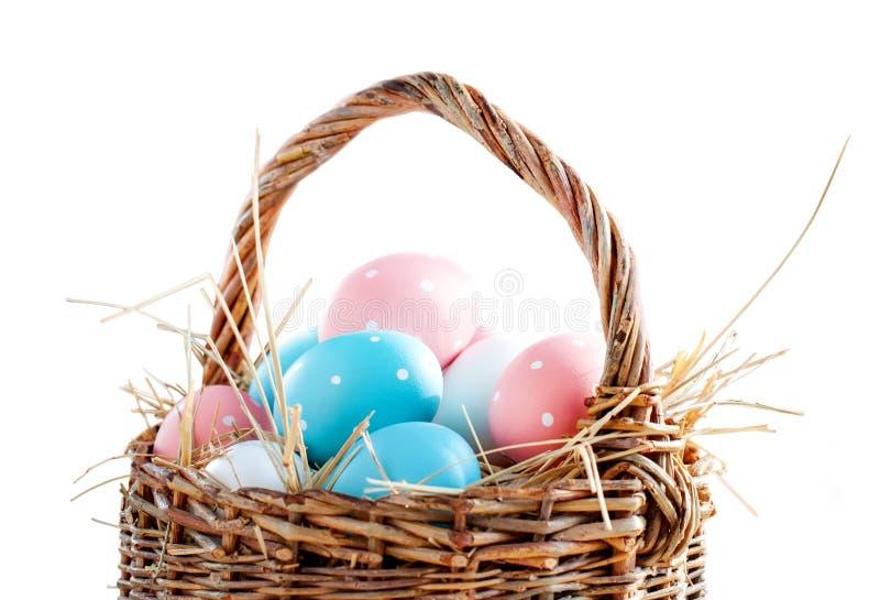 Os ovos da páscoa pintaram ervilhas azuis cor-de-rosa no branco isolado cesta foto de stock royalty free