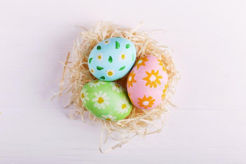 Os ovos da páscoa pintaram flores à mão, em um ninho em uma tabela branca Preparação para o feriado fotografia de stock royalty free
