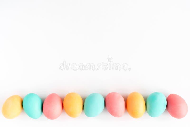 Os ovos da p?scoa coloridos alinharam no fundo branco Configura??o lisa foto de stock