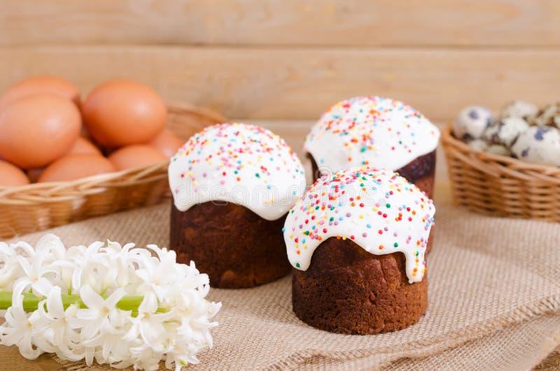 Os ovos de codorniz, galinha eggs em uma cesta, bolo da Páscoa na madeira rústica imagem de stock