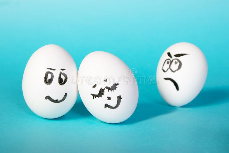 Os ovos de galinha com caras pintadas O homem descontentado olha os pares felizes jealousy Fundo para um cartão do convite ou uma foto de stock
