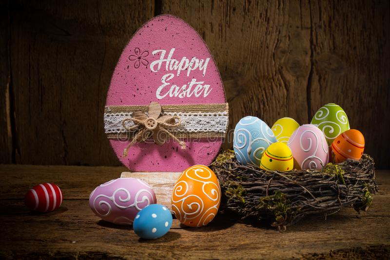 Os ovos felizes pintados coloridos do cartão de easter nos pássaros aninham a cesta no fundo de madeira rústico imagens de stock